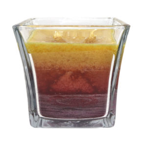 tri coloured candle in a glass container
