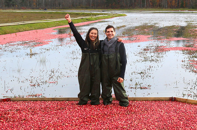 couple standing in floating cranberries waving