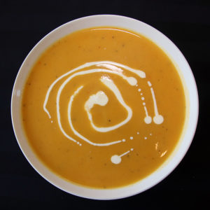 bowl of butternut squash soup with swirl of sour cream