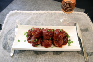 spicy turkey meatballs with cranberry glaze on a plate with a glass of wine