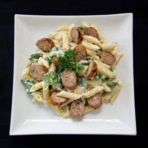 plate of smoked goat cheese alfredo with turkey sausages