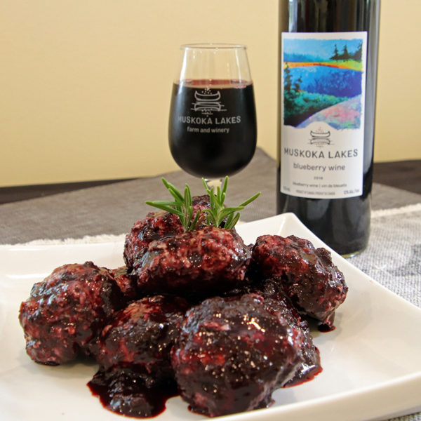 blueberry balsamic turkey meatballs on a plate with blueberry wine in the background