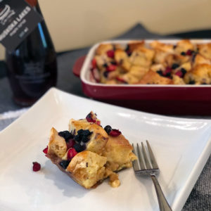 cranberry blueberry french toast bake on a plate with maple syrup in background