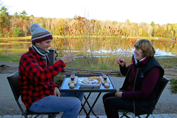 two people with wine and cheese on a patio with a view of water and trees