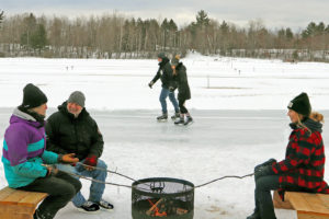 people in winter around a fire pit with skaters in the background