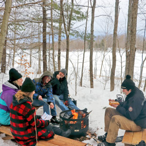 people around a fire pit in winter roasting marshmallows